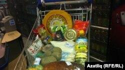 Товары из потребительской корзины в тележке из супермаркета. Иллюстративное фото.
