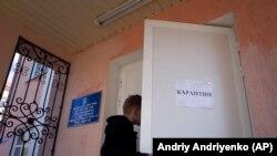 Ілюстрацыйнае фота. Хлопчык адчыняе дзьверы пустога клясу з плякатам, які абвяшчае карантын у сярэдняй школе ў Краматорску, Усходняя Ўкраіна