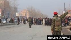 Сотрудники афганских сил безопасности на месте взрыва автобуса в Кабуле. 26 января 2014 года.