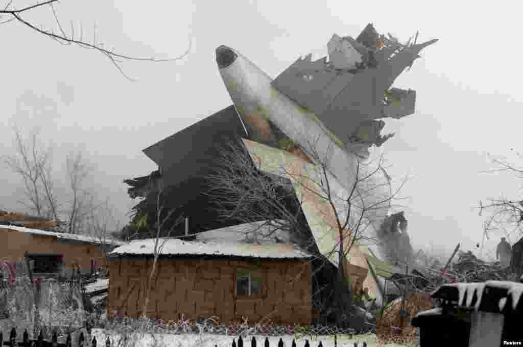 The tail section of the Boeing 747 lying among damaged houses in Dacha-Suu, outside of the capital, Bishkek.
