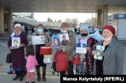 Other Kazakhs hold photos of their relatives trapped in China's Xinjiang region.