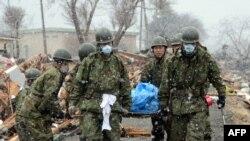 Военные выносят тело очередной жертвы цунами, обнаруженное среди обломков дома