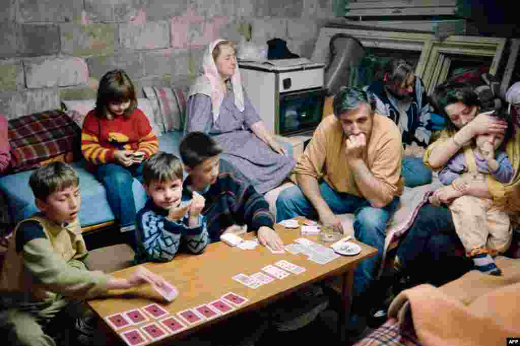 A family takes shelter in a cellar in Sarajevo on June 6, 1992, as shells fall on the Bosnian capital. The fighting continued, despite a UN-brokered deal to reopen the airport and for Serbian troops to withdraw from their barracks in the center of the city.