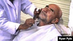 China - A man receives a shave from a street barber in Kashgar, 03Nov2006