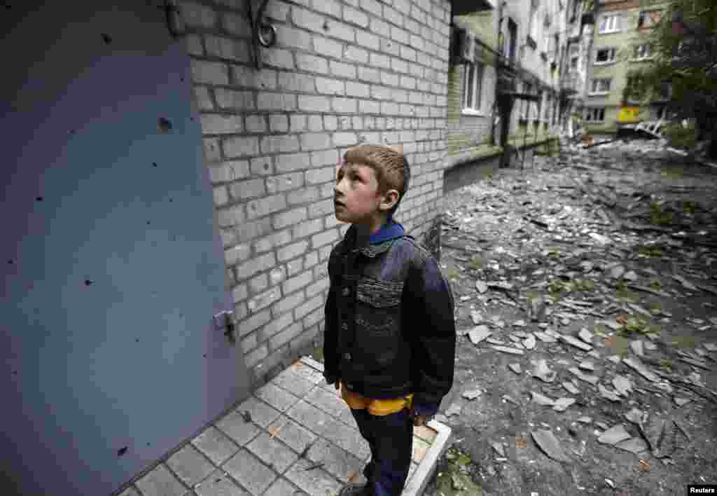 A boy looks at shrapnel holes on the door of a residential building, damaged by what locals say was overnight shelling by Ukrainian forces in the eastern town of Slovyansk on June 12. (Reuters/Gleb Garanich)
