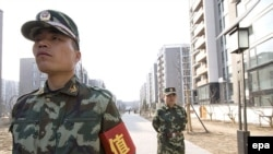 Security guards patrol Beijing's new Olympic Village