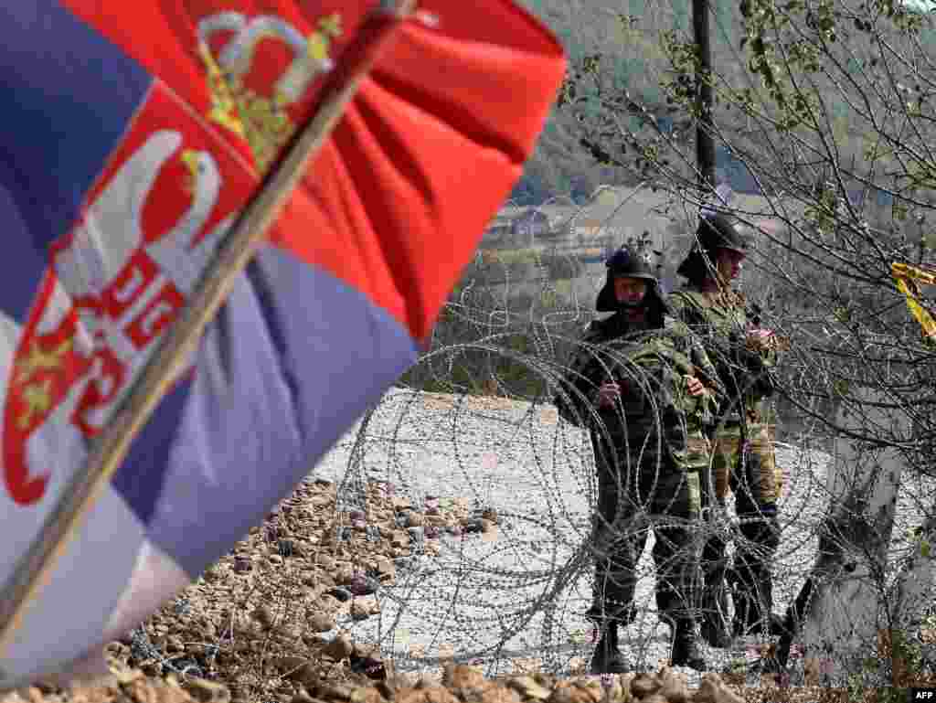A Serbian flag is seen as KFOR soldiers stand guard at a barricade at the Jarinje border crossing between Serbia and Kosovo. (AFP photo/Sasa Djordjevic)