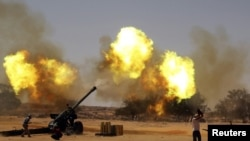 NTC fighters fire a howitzer at Qaddafi loyalist forces east of Sirte on September 16.