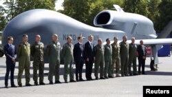 Генсекретар НАТО Єнс Столтенберґ та офіційні особи-учасники саміту позують на тлі безпілотника Північноатлантичного альянсу, Варшава, 8 липня 2016 року