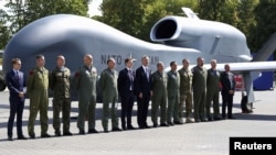 NATO Secretary-General Jens Stoltenberg (center) with officials and military personnel in front of a NATO drone outside the venue of the Warsaw Summit.
