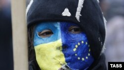 Ukraine -- A demonstrator wears a facemask painted in EU and Ukrainian national colours during a mass rally called For European Ukraine in central Kyiv, November 24, 2013