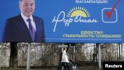 """Прохожие рядом с предвыборным билбордом партии """"Нур Отан"""". Алматы, 11 марта 2016 года."""