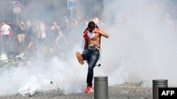 Ресей мен Англия футбол жанкүйерлері қақтығысы кезінде көзден жас ағызатын газ баллонын теуіп жатқан фанат. Франция, Марсель, 11 маусым 2016 жыл. (Көрнекі сурет)