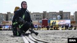 یک زن آتشنشان در مانور آتشنشانان در مشهد