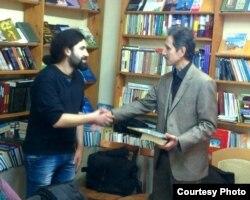 Bakı Kitab Klubun direktoru Elxan Rzayev (sağda) Qurban Məmmədlini mükafatlandlrlr.