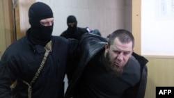 Вооруженный полицейский в маске ведет Тамерлана Эскерханова в суд. Москва, 8 марта 2015 года.