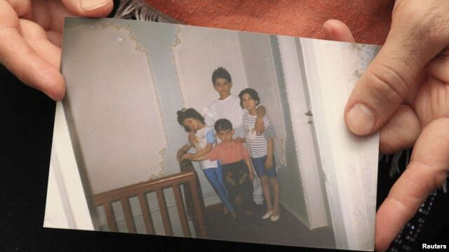 Patimat Suleimanova, an aunt of Boston bombing suspects Dzhokhar and Tamerlan Tsarnaev, holds a family photo at her house in Makhachkala showing the two as young boys .