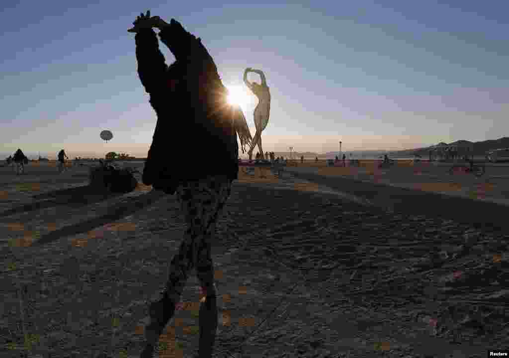 "Rochelle Schieck dances near the ""Truth is Beauty"" sculpture, by Marco Cochrane, at the 2013 Burning Man arts and music festival in Nevada."