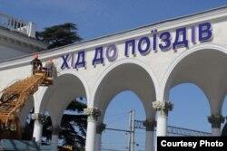 Рабочие снимают вывеску на украинском языке с колоннады железнодорожного вокзала в Симферополе, 22 мая 2014 года