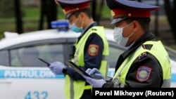 Сотрудники дорожной полиции на пропускном посту в Алматы.