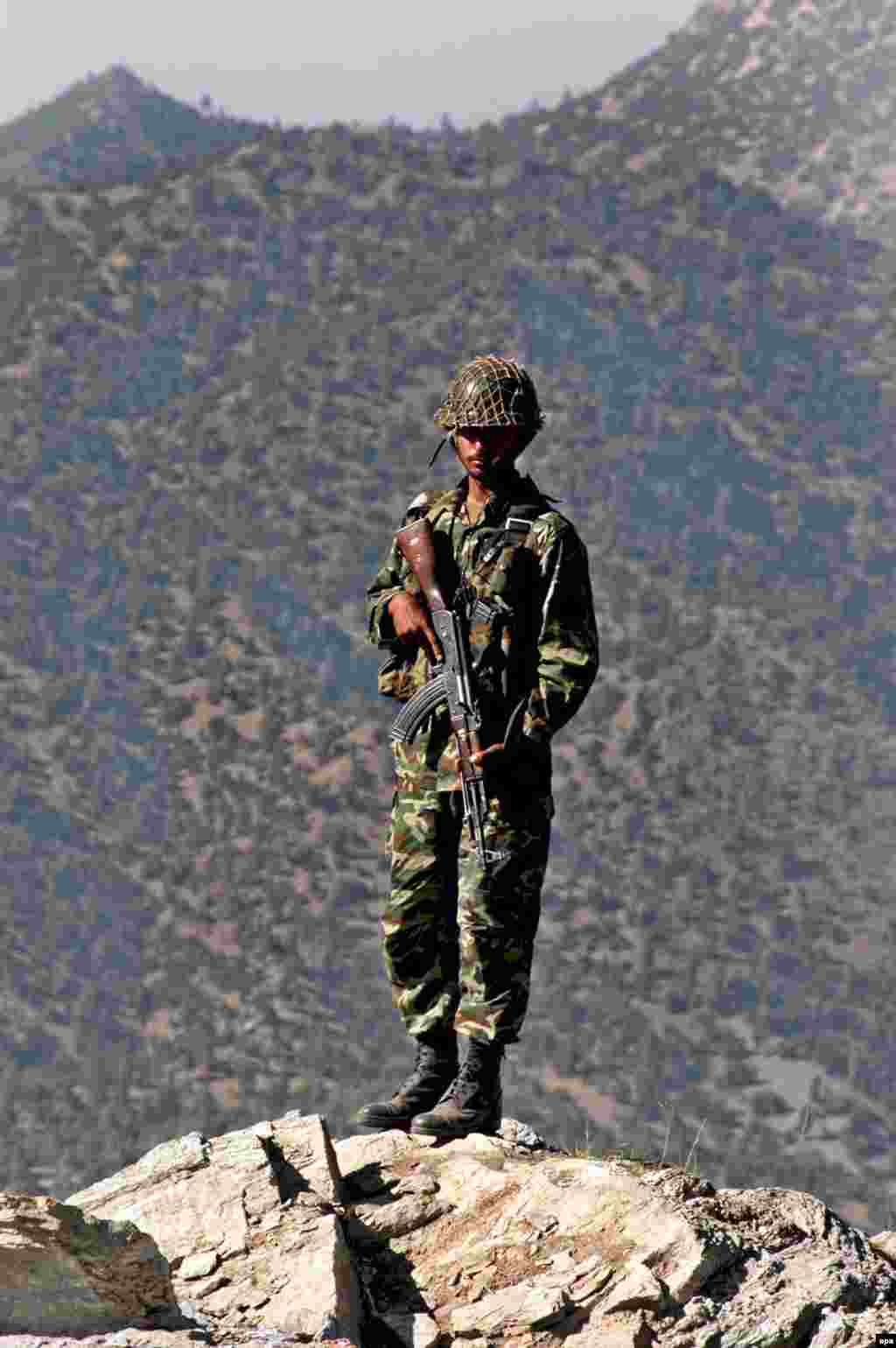 A Pakistani soldier monitors the Afghan-Pakistan border in 2005 (epa) - The challenge of uprooting the insurgents is hard because many are based in tribal parts of Pakistan. The ease with which they cross the long border has aggravated long-standing tensions. Pakistani forces launched major operations in 2006 in border areas, but suspicions remain in Afghanistan that some in Islamabad are keen to keep Afghanistan a weak client state.