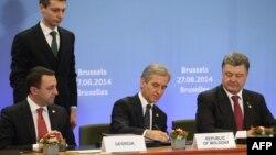 Belçikada Gürcüstanın Baş maziri İrakli Garibashvili, (solda) Moldovanın Baş naziri İure Leanca (ortada) və Ukraynanın prezidenti Petro Poroshenko (sağda) tAvropa Birliyi ilə assosiasiya sazişi imzalayırlar. 27 iyun 2014