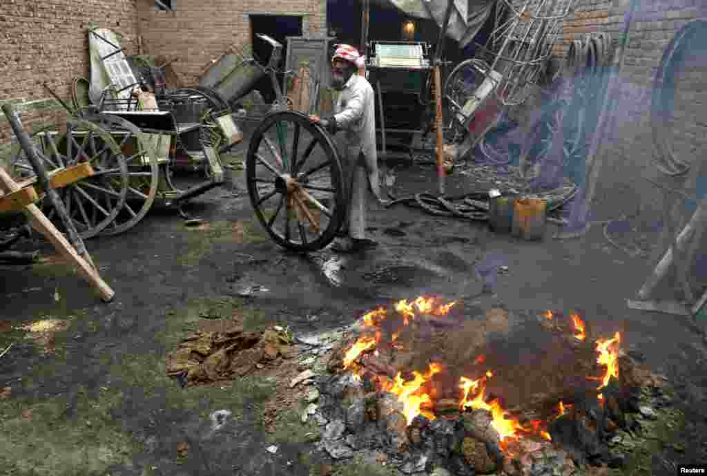 A worker burns waste rubber and cow-dung cakes for heat as he repairs wheels for carts pulled by livestock in Peshawar, Pakistan. (Reuters/Khuram Parvez)
