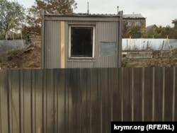 Вагончик і будівельний паркан на захопленій ділянці
