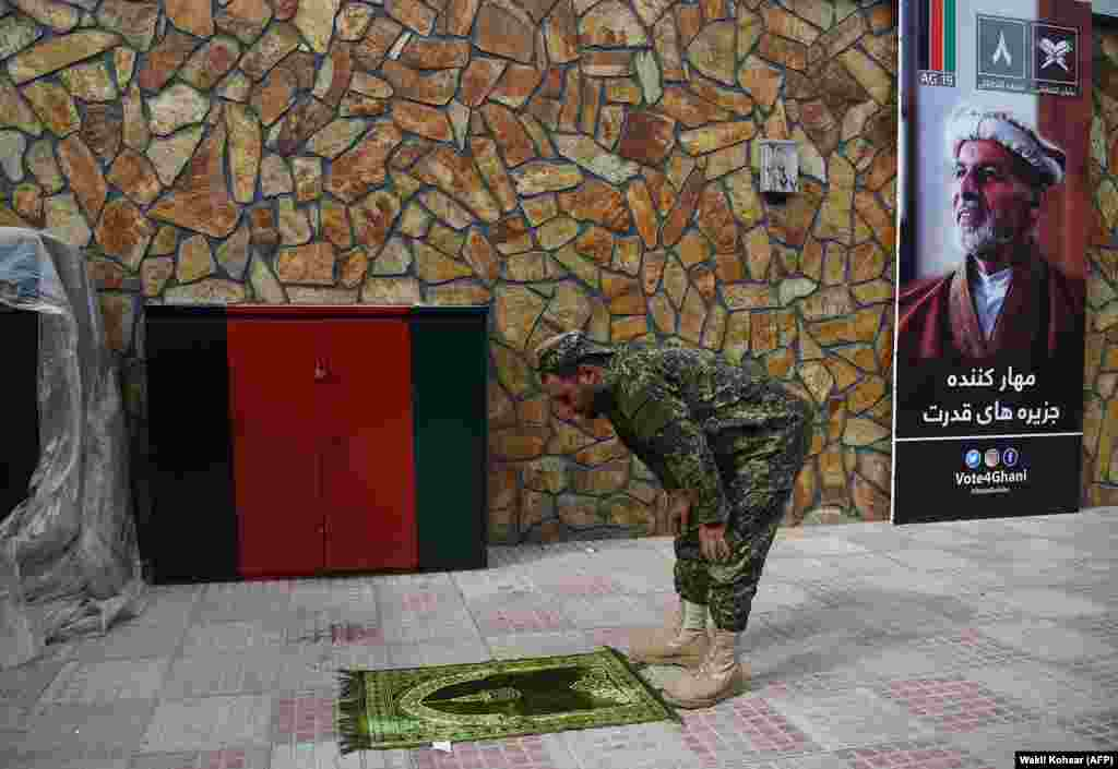 A security officer prays next to a poster of Afghan presidential candidate Ashraf Ghani at his campaign headquarters' call center in Kabul during the election on September 30. (AFP/Wakil Kohsar)