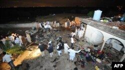 Pakistani rescue workers and local residents search the site of the plane crash in Islamabad on April 20.