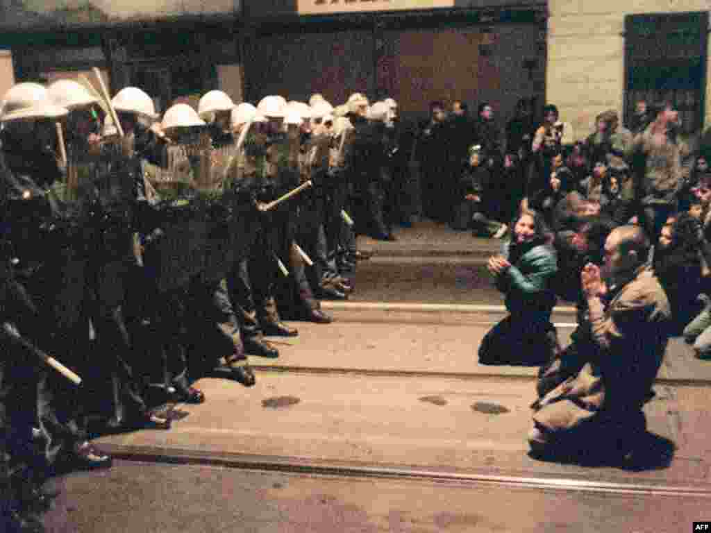 In this photo, also taken on November 19, protesters kneel as they face riot police in downtown Prague. The police again responded with violence.