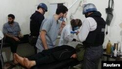 БҰҰ ұйымының химиялық шабуылды зерттеуге барған сарапшылары ауруханаға түскен азаматты тексеріп жатыр. Сирия, Дамаск, 26 тамыз 2013 жыл.