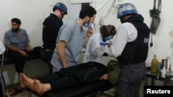 БМО белгечләре хастаханәдә химик коралдан зыян күргән дип шикләнелгән кешеләр янында. 26 август 2013