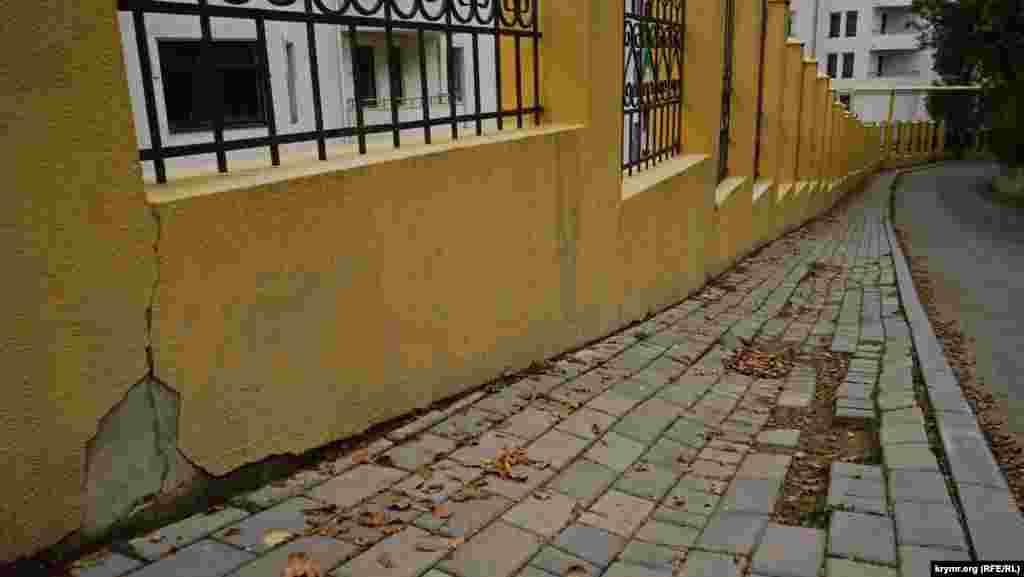На паркані новобудови і новому тротуарі видно наслідки нещодавнього зсуву