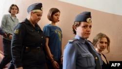 Участницы группы Pussy Riot Надежда Толоконникова (в центре), Мария Алёхина (справа) и Екатерина Самуцевич (слева) в сопровождении полицейских идут в зал суда. Москва, 17 августа 2012 года.