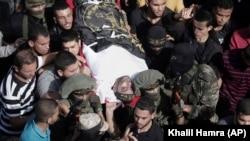 اعضای سازمان جهاد اسلامی در حال حمل پیکر یکی از شبهنظامیان این گروه که نزدیک به دو هفته پیش در جریان تخریب تونل کشته شده بود.