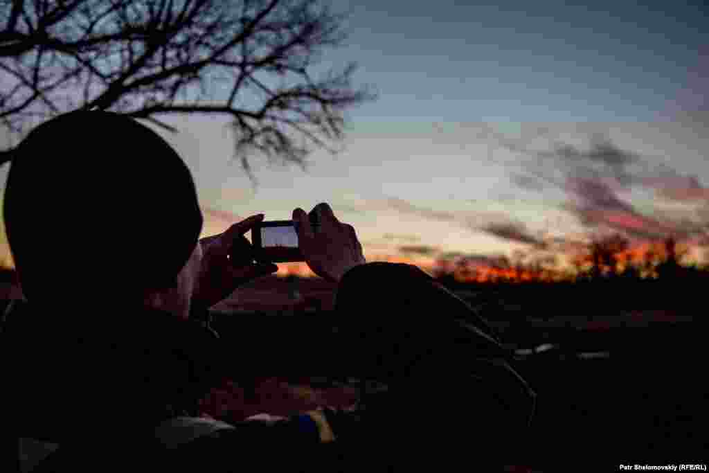 In a calm moment, a Ukrainian government serviceman takes a picture of the sunset.