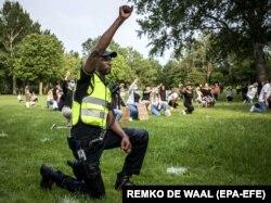 Mișcarea Black Lives Matter a cuprins întreaga lume. Aici, un polițist olandez îngenunchează în semn de solidaritate (17 iunie 2020)