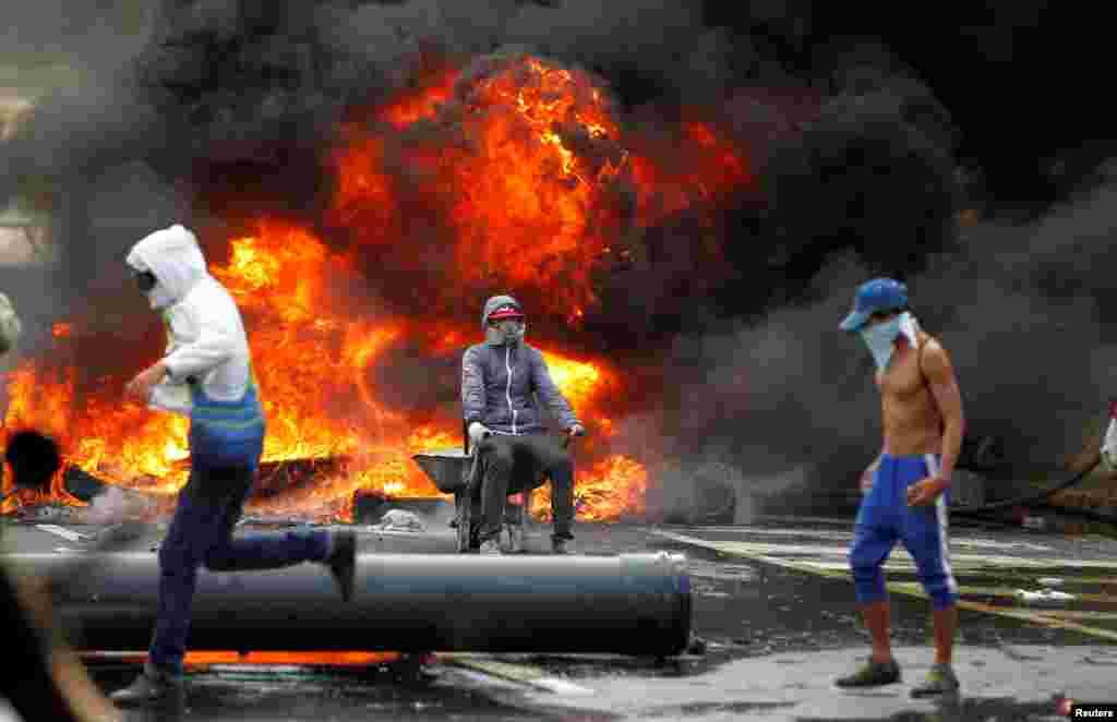 Третий год в Венесуэле продолжаются протесты из-за нехватки продуктов питания и медикаментов. Страна по сути находится в режиме чрезвычайного положения. Почти два миллиона человек подписали петицию за отставку президента Мадуро, а в столице уже третий год десятки тысяч венесуэльцев регулярно выходят на акции протеста. На фото – демонстранты на фоне горящих покрышек в Каракасе, столице Венесуэлы. 24 апреля 2017 года.