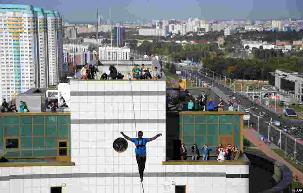 Ukrainian slackliner Stanislav Panyuta balances as he walks on a highline from the rooftop of a building in Minsk. (AFP/Sergei Gapon)