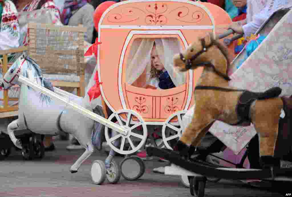 A girl looks out of her stroller decorated as a coach during a pram parade on International Children's Day in the town of Mohilev, Belarus, on June 1. ( AFP/Sergei Gapon)
