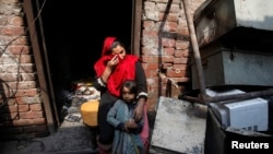 Anzila Semeul cries while sitting with her daughter in front of their home after it was lit on fire by a mob two days earlier, in Badami Bagh, Lahore, in March 2013.