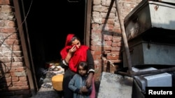 Anzila Semeul cries while sitting with her daughter in front of their home, after it was burnt by a mob on March 9, in Lahore on March 11.
