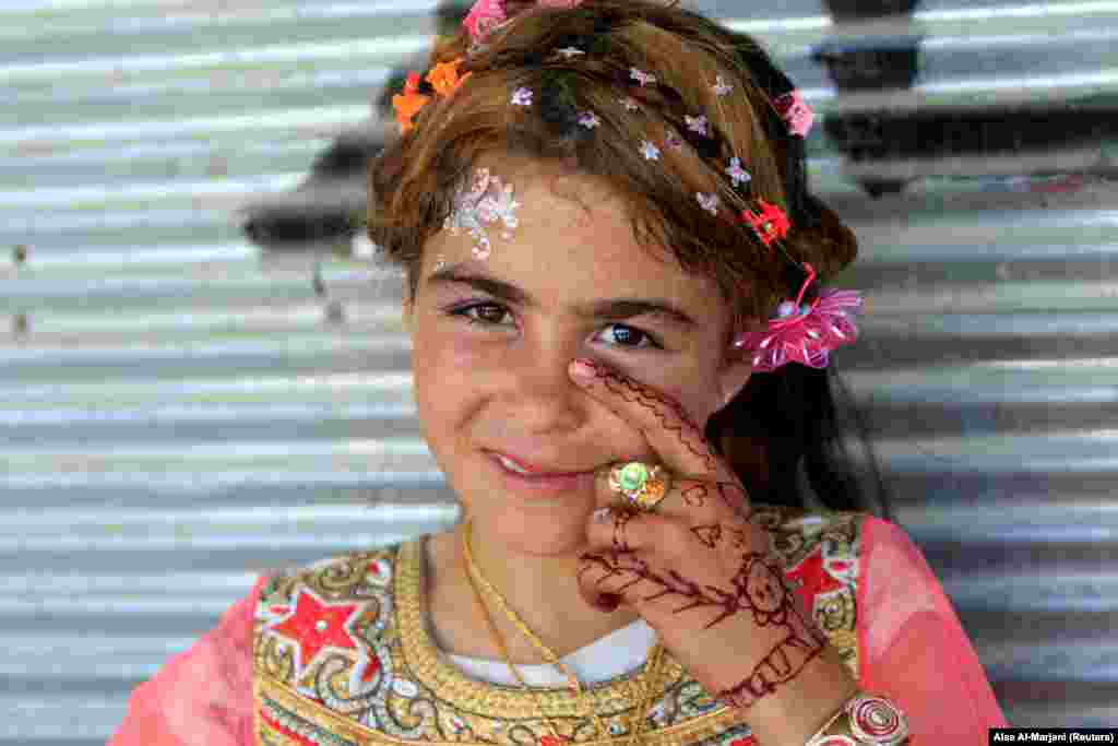 An Iraqi girl is seen as she celebrates Eid al-Fitr, a festival to mark the end of the Muslim holy month of Ramadan, in Mosul. (Reuters/Alaa Al-Marjani)