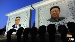 Arxiv fotosu: Şimali Koreyada adamlar ölkənin qurucu lideri adlanan Kim İl-Sung və onun oğlu Kim Jong-İl-in portretinə təzim edirlər. 9 aprel 2012