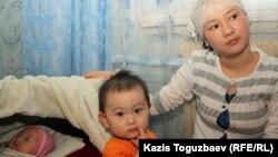 Азаптаудан мерт болған Базарбай Кенжебаевтың кіші қызы Жадыра Кенжебаева екі жасар баласы Аружан және нәрестесі Айсұнамен бірге. Маңғыстау облысы Қызылсай кенті, 14 ақпан 2012 жыл.