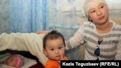 Жадыра Кенжебаева қыздары - екі жасар Аружан мен бесіктегі Айсунаның қасында отыр. Маңғыстау облысы, Қызылсай ауылы, 14 ақпан 2012 жыл.