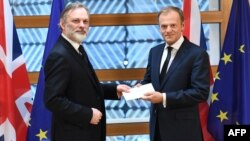 Britain's ambassador to the EU, Tim Barrow (left), delivers the formal notice of the U.K.'s intention to leave the bloc under Article 50 of the EU's Lisbon Treaty to European Council President Donald Tusk in Brussels on March 29.