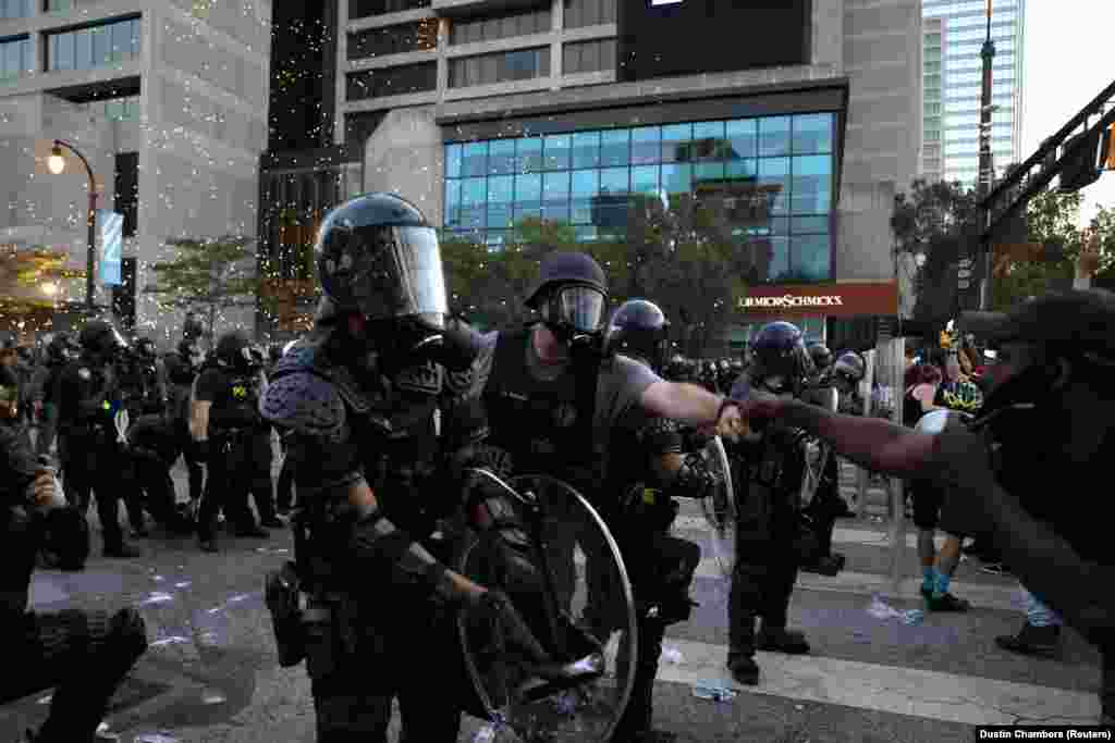 Një zyrtar policor shkëmben një përshëndetje me një protestues, teksa policia tenton të ndalojë përshkallëzimin e situatës pas protestave të lidhura me vdekjen e Floydit.