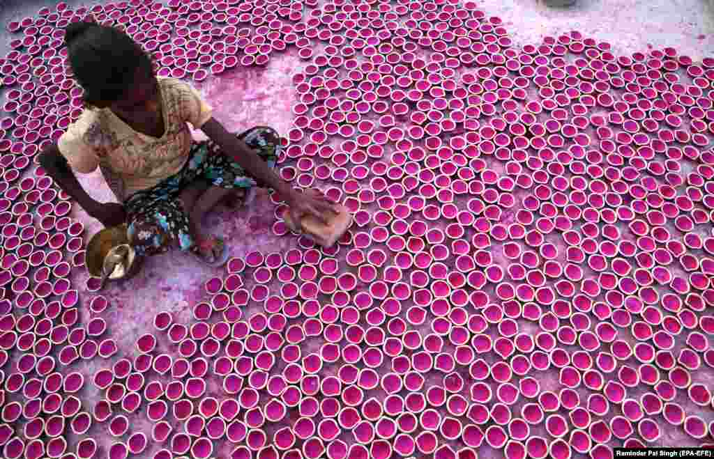 "An Indian girl arranges freshly painted ""Diya"" or earthen lamps for drying at her family's home workshop in Amritsar. (epa-EFE/Raminder Pal Singh)"